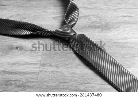 Dark grey tie on the floor in black and white - stock photo
