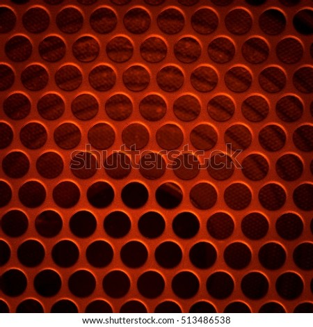 Dark grid background. Close up of aluminum speaker. Texture with holes.