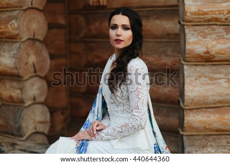 Dark hair envelopes a tender woman's face while she sits behind a wooden wall