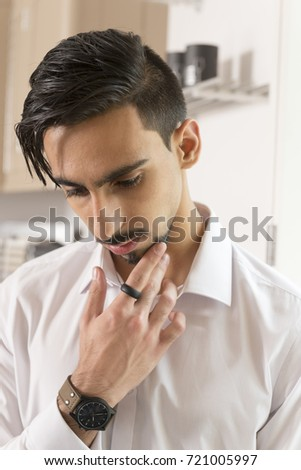 Dark-haired bearded young man in a fashionable white office long sleeve shirt