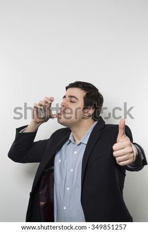 Dark-haired european businessman with a perky look gives a thumps-up while drinking from a glas of water in the other hand while in front of a gradient background