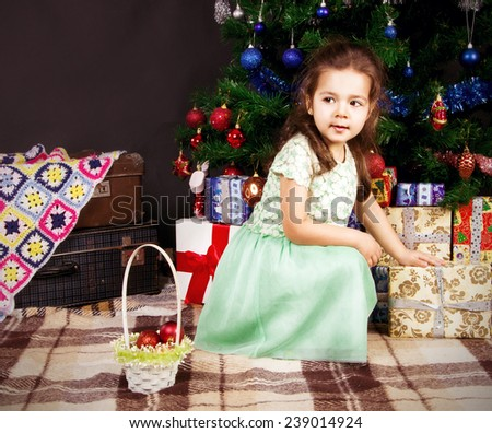 dark-haired girl in a dress sitting with gifts near a Christmas tree and looks aside - stock photo