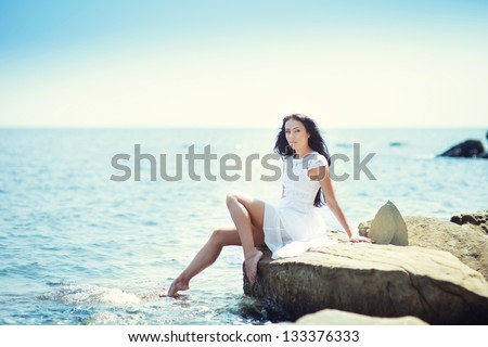 dark-haired girl in a white dress at the sea