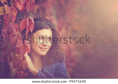 Dark-haired girl in autumn park, closeup portrait - stock photo
