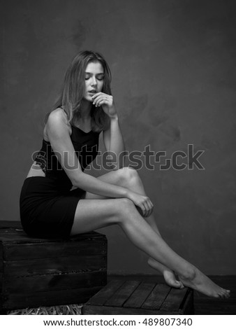 Dark-haired girl sitting on vintage boxes in the Studio.Black and white photos were taken against a gray wall.She is dressed in clothes of dark tones.Photos are taken close up and full length.