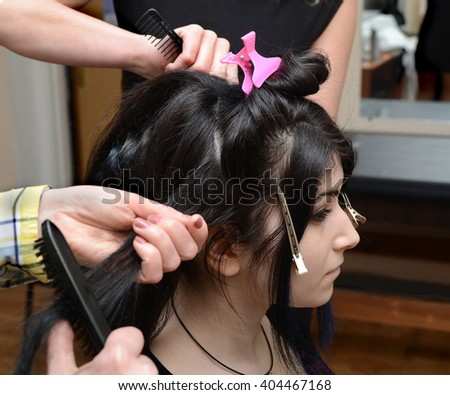 dark-haired girl to do a coiffure in a hairdressing salon - stock photo