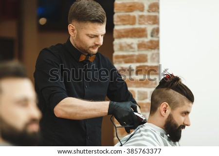 Dark haired man wearing black shirt doing a haircut for man with long black hair at barber shop, copy space.