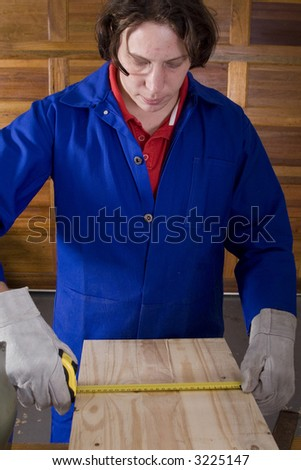 Dark haired man with blue overall measuring wood with gloves - stock photo