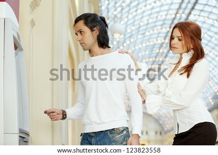 Dark-haired man with credit card and red-haired woman stand near to cash dispenser - stock photo