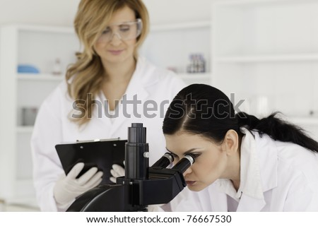Dark-haired scientist and her assistant conducting an experiment in a lab
