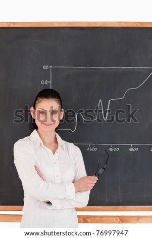 Dark-haired scientist explaining charts while looking at the camera - stock photo