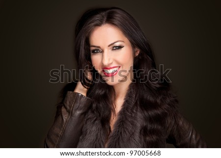 Dark haired smiling beautiful woman in a fashionable jacket against a dark background - stock photo