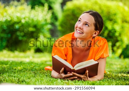 Dark-haired smiling beautiful young woman in orange blouse lying on grass and reading book, against green of summer park. - stock photo