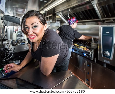 Dark haired smiling cashier with blue eyes on food truck - stock photo