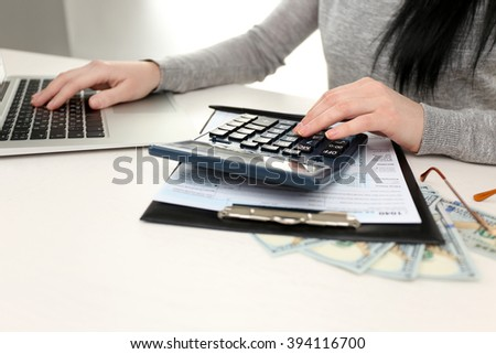 Dark-haired woman calculating while using computer on the white wooden table, close up
