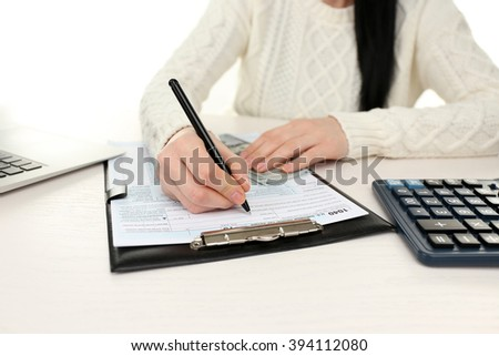 Dark-haired woman holding a pen and using filling in the individual income tax return on the white wooden table, close up