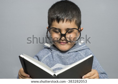dark-haired young student reading a funny book, reading and learning