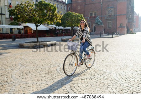 Dark-haired young woman in sunglasses rides by bicycle on a paved pavement. Solar morning. Beautiful buildings of the ancient European city, a monument, green trees. Woman in a good mood, she smiles.