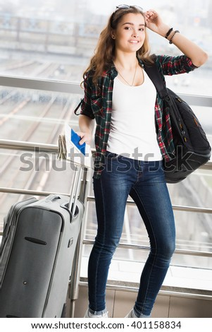 dark-haired young woman standing with a suitcase and a backpack and holding a passport with a ticket. Full length. tourism concept