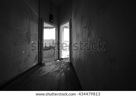 Dark hallway of a deserted building in a ghost town with desert sanding filling the rooms.