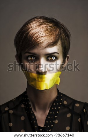 Dark Headshot Of A Distressed And Oppressed Woman Bound And Gagged In Silence With Yellow Masking Tape Covering Her Mouth In A Speak No Evil Conceptual - stock photo