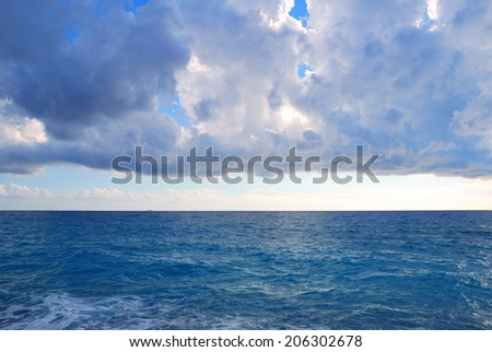 Dark heavy clouds and vast deep blue sea waters - stock photo
