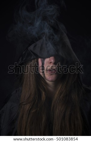 Dark hooded woman assassin letting smoke out her mouth, gothic and halloween concept