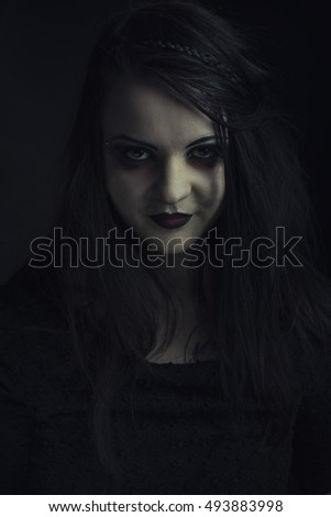 Dark horror gothic girl, pale face and smiling with bad intentions