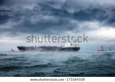 Dark image of tanker and tugboats on sea during a violent blizzard. - stock photo
