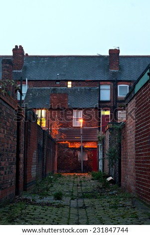 Dark inner city alleyway with lights at dawn - stock photo
