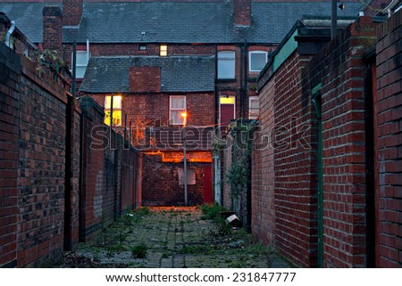 Dark inner city alleyway with lights at dawn