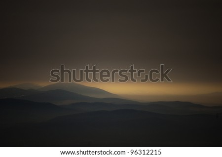 dark landscape with mountains at sunset - stock photo