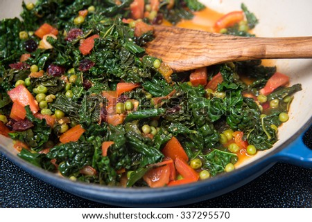 Dark Leafy Greens Cooked with Tomatoes, Peas and Cranberries for Healthy Side Dish or Lunch - stock photo