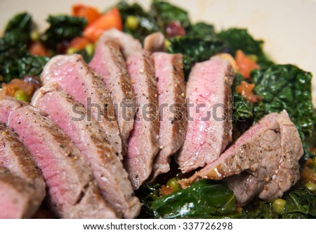 Dark Leafy Greens Cooked with Tomatoes, Peas and Cranberries. Served with Sliced Grass Fed Steak.