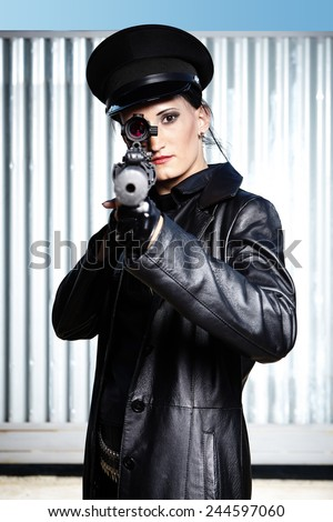Dark military woman armed with shotgun in ruins of old factory building waiting for target - stock photo