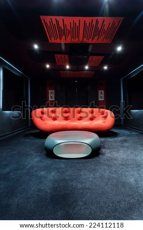 Dark modern interior with red sofa in the centre - stock photo