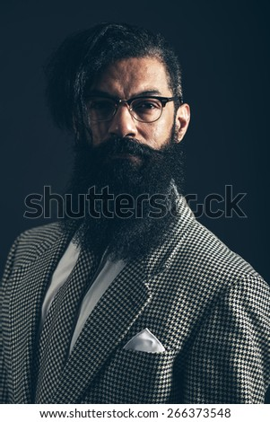 Dark moody portrait of a man with a big bushy beard wearing glasses and a stylish checked suit looking at the camera with a serious expression - stock photo