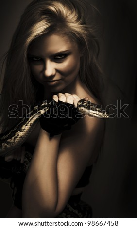 Dark moody portrait of a mysterious blonde sorceress holding the head of a python in her hand - stock photo