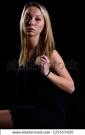 Dark moody portrait of a sophisticated blonde woman in evening wear looking down at the camera with a serious expression, conceptual of nightlife - stock photo