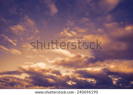 Dark moody stormy sky with clouds, abstract nature background with purple orange toned photo filter effect - stock photo
