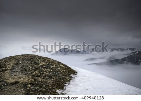 Dark mountain landscape. Snowy mountains in the deep fog. No Man's land - stock photo