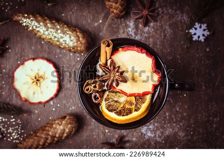 dark mulled wine cup with fruits and winter spices, on wooden background , top view, toned - stock photo