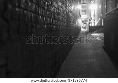 dark narrow alleyway at night, with street light illuminating the scene. Has selective focus.  - stock photo