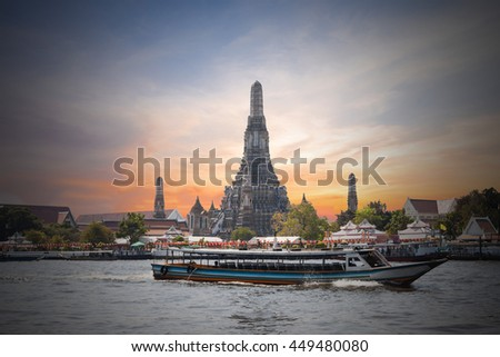 Dark of The Temple of Dawn, Wat Arun, on the Chao Phraya river with passenger ships or boat and a beautiful sky in twilight time at Bangkok, Thailand - stock photo