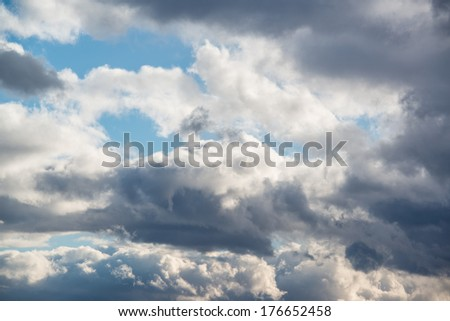 Dark ominous grey storm clouds with sun shining through still. Dramatic sky. - stock photo
