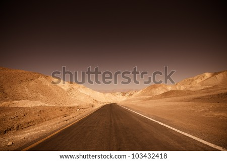 Dark, ominous road leading through desert of badlands Death Valley National Park - stock photo
