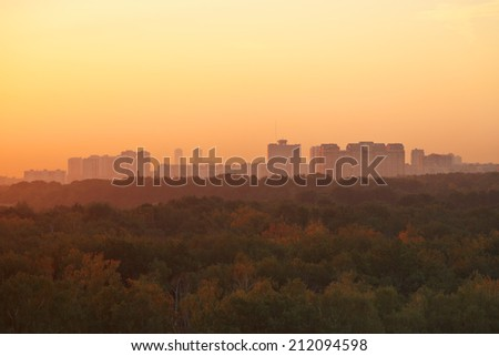 dark orange early sunrise over urban houses and park in summer morning - stock photo