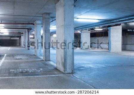 Dark parking garage industrial room interior with blue light - stock photo