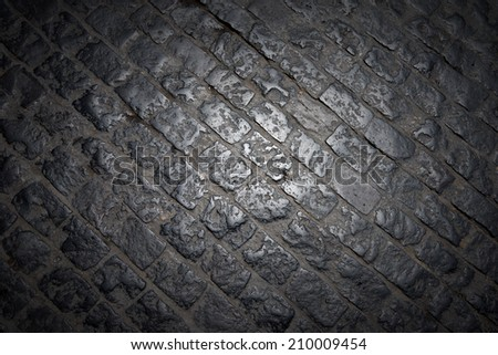 Dark Paving Stone Roadway / Dark black background with irregular stones and central light - stock photo