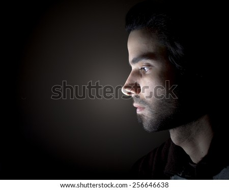 Dark portrait of a face in profile - stock photo